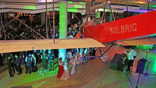 The benoist biplane that was built and flown Oscar and Mary Solbrig of Davenport before 1910 hangs above the Jaguar students at the 2017 Ankeny Centennial High School Junior / Senior Prom at the State Historical Building in Des Moines.