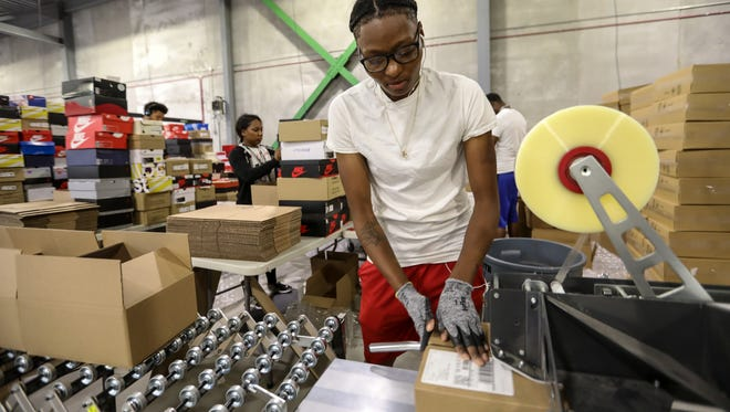 Calais Sewell, 27, of Detroit prepares authenticated goods for shipping at the new Stock X operations center on Tuesday, July 3, 2018.