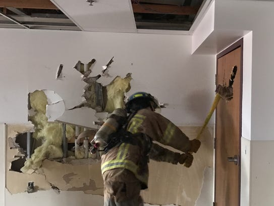 Using an axe, a student with Howell High School's Firefighter