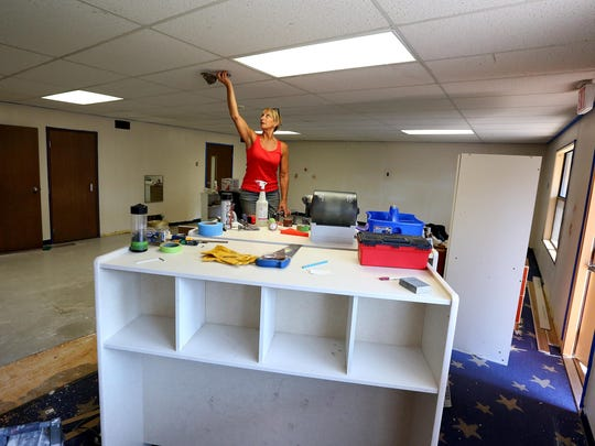 Ann Rogers removes tape and other items from the ceiling at the new Montessori Discover Academy at 875 Promontory Place SE, Wednesday, August 12, 2015, in Salem, Ore.