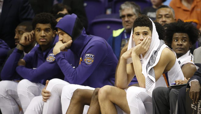 Suns' Devin Booker watches with a towel over his head after fouling out in the fourth quarter against the Nets at Talking Stick Resort Arena in Phoenix, Ariz. on November 6, 2017.