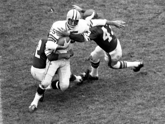 Green Bay Packers receiver Max McGee is tackled by Minnesota Vikings cornerback Dick Pesonsn (22) and defensive back Will Sherman (43) at Metropolitan Stadium in Bloomington, Minn., on Oct. 22, 1961.