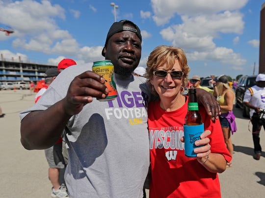 Detroit Harris, an Louisiana State University fan and father of starting quarterback Brandon Harris, tries a Wisconsin beer courtesy of Anne Hale of De Pere at Lambeau Field before the UW-LSU game September 3, 2016.