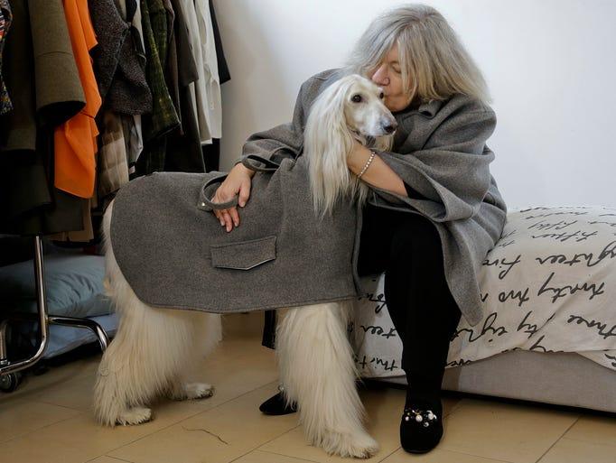 Designer Giovanna Temellini kisses her dog Ulisse,