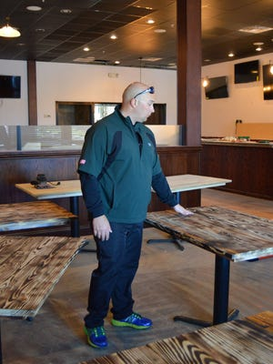 Steve Hagen, owner of new restaurant Hooked Up, inspects the restaurant's new tables. Hooked Up will have 24 taps available, three pool tables, two dozen flat screen TVs and will serve refined pub food.