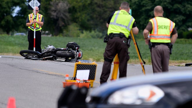 Investigators on the scene of a fatal car and motorcycle accident at Hartel Rd. and St. Joseph Highway south of Grand Ledge Tuesday.
