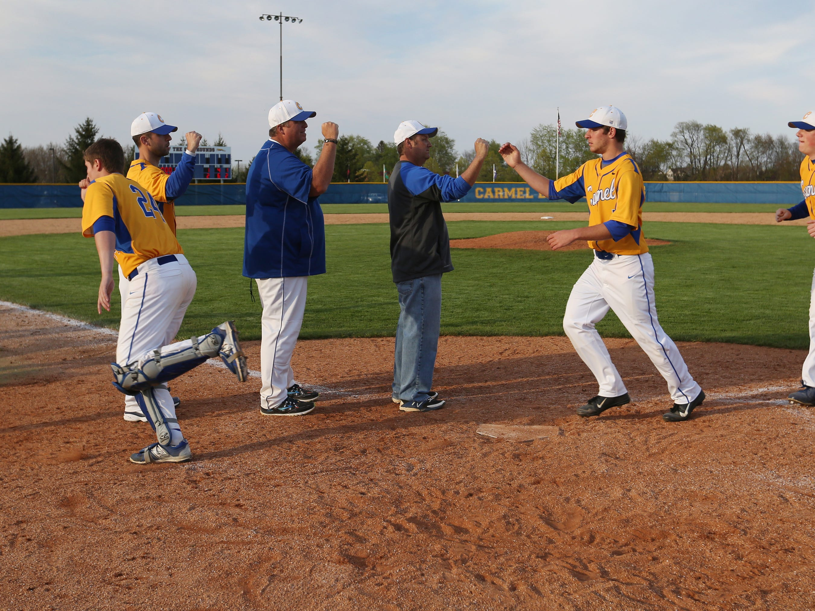 Carmel players celebrate their 2-1 victory over Lawrence North, as Carmel pitcher Tommy Sommer held the Wildcats to four hits and gave Lawrence North its first loss of the season, at Hartman Field in Carmel on Wednesday, April 29, 2015. Lawrence North (14-1) took a 1-0 lead in the top of the fifth inning, but Carmel (7-7) came back to tie it in the bottom of the inning, then scored the winning run in the bottom of the 6th.