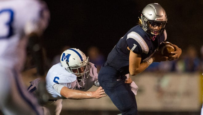 Reitz quarterback Eli Wiethop (1) gets tackled by Memorial's Brock Combs (6) Friday night at Reitz Bowl .