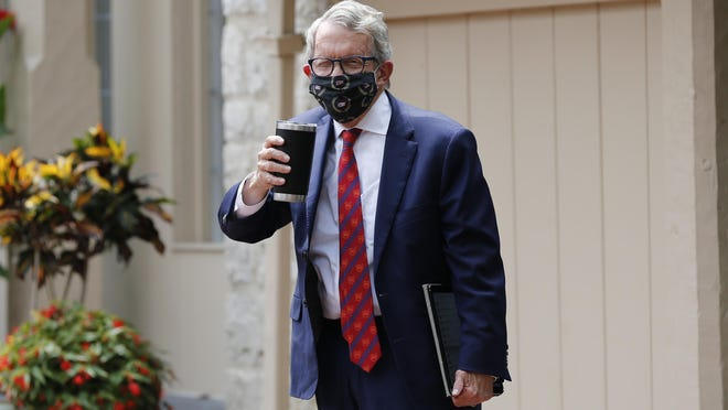 Ohio Gov. Mike DeWine acknowledges members of the media while entering his residence after testing positive for COVID-19 earlier in the day Thursday, Aug. 6, 2020, in Bexley, Ohio.