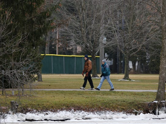 Two people take a stroll through Bukolt Park in Stevens