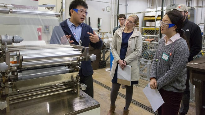 Wisconsin paper and packaging industry professionals attended a course on coating and lamination in packaging on Jan. 21 at the University of Wisconsin-Stevens Point, offered by the Wisconsin Institute for Sustainable Technology.  At left, Roland Gong, assistant professor of paper science and engineering, provides details about a state-of-the-art pilot coating and lamination line and the paper machine to Kelly Helein of Daikin America, Appleton; and Lily Xiao of Georgia-Pacific, Neenah, among others. This is one of a series of courses offered throughout the year to industry professionals taught by WIST staff and Paper Science and Engineering faculty on campus.