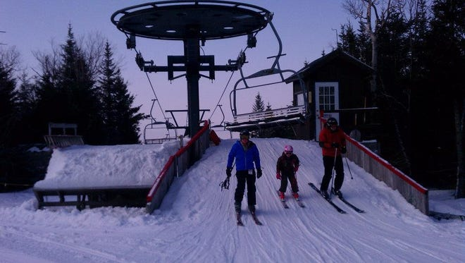 From left, three generations of the Waite family from Burlington -  grandfather Bobby, granddaughter Olivia, 7, and son/dad Jared - unload from the Timberline Quad at Bolton Valley Resort during opening weekend in 2012. This winter's opening at Bolton has been delayed a week, to Dec. 19, by warm temperatures.