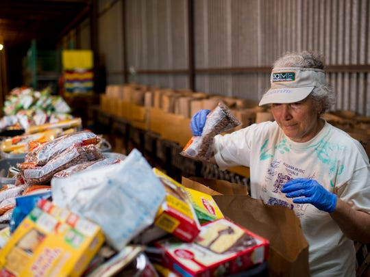 Volunteer Jane Rosen fills bags with food supplies at the FoodNet warehouse in Lafayette, LA, Wednesday, April 1, 2015.