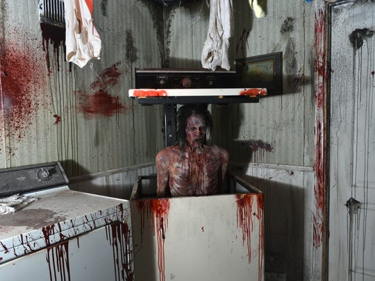 A ghoulish figure bursts from a washing machine in the laundry room of the classic Victorian house portion of the Reign of Terror that opens Saturday at the Janss Marketplace in Thousand Oaks.