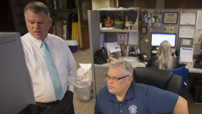 Steve DuBois (left), director and coordinator, chats with fellow IMPD officer Stephen Harris at Crime Stoppers headquarters, which is in an industrial warehouse on Indianapolis' west side. The nonprofit collects tips for more than 50 law enforcement agencies across 17 counties in Central Indiana.