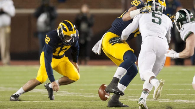 Michigan punter Blake O'Neill bobbles a low snap before fumbling it on the last play of the game against Michigan State.