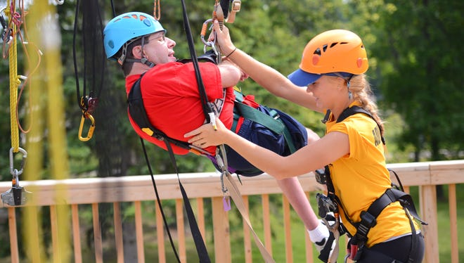 The NEW Zoo Adventure Park zip line hosted a group of physically handicapped adventurists Aug. 11, 2014.  Jeff Zander arrives at the landing platform after his ride on the zip line wire.