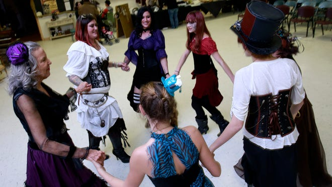 Revelers get up to dance during the Steamers & Dreamers convention on Saturday at the Aztec Senior-Community Center.