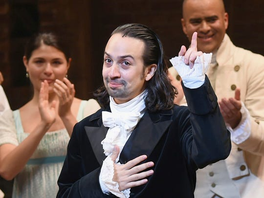 """Hamilton"" creator Lin-Manuel Miranda, foreground, gestures during his final performance curtain call in New York."