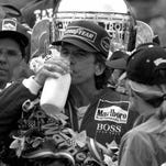 Emerson Fittipaldi holds the bottle of mile he was given after his victory in the 500-Mile Race. He took a swig of orange juice first.