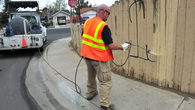 Brian Suhl covers graffiti at Ninth Street and Inyo Way in Reno in 2013.