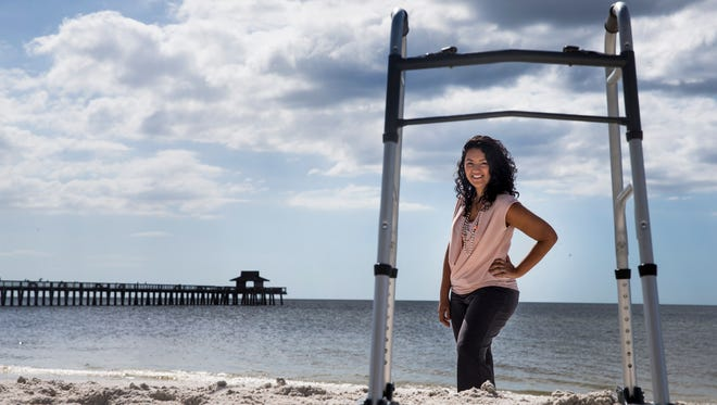 Stephanie Gomez, the co-founder, president and CEO of Stabilized Steps, stands near a prototype of the Stability Glider on the beach in Naples on Wednesday, Oct. 11, 2017. The company's patented Stability Gliders attach to the bottom of medical walkers to make them more stable on sand, gravel and mud.
