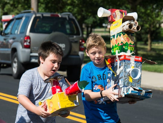 Two students carry their projects down Quantico Road