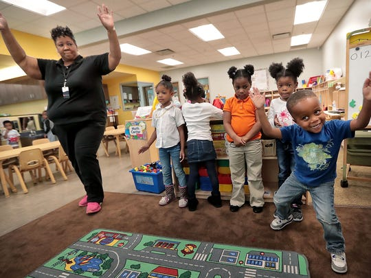 Julius Blair (right) is the first to get in the groove as lead teacher Yolanda Ford (left) tries to wake up her class with a sing-along after nap time at Porter-Leath's Early Childhood Academy Thursday afternoon.