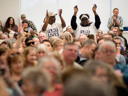 """People cheer wearing """"Flint Lives Matter"""" t-shirts during a public hearing on a Nestle Waters North America's proposal to boost the volume of groundwater it pumps for bottling on Wednesday, April 12, 2017 in Big Rapids, Mich.  The company wants to withdraw up to 400 gallons per minute from a well in Osceola County — up from 150 gallons per minute. The request is pending with state regulators."""