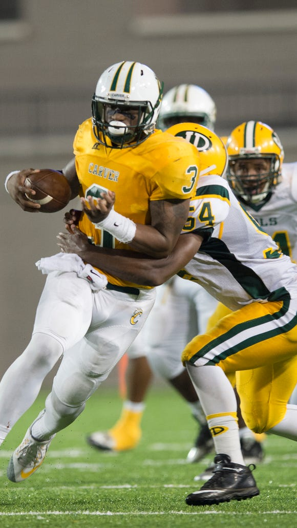 Carver linebacker Lyndell Wilson (3) runs downfield as Jefferson Davis  Tydarius Iverson (54) attempts to tackle him during the AHSAA football game on Thursday, Oct. 29, 2015, at the Cramton Bowl in Montgomery, Ala.