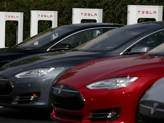 Tesla Model S sedans are parked in front of a row of