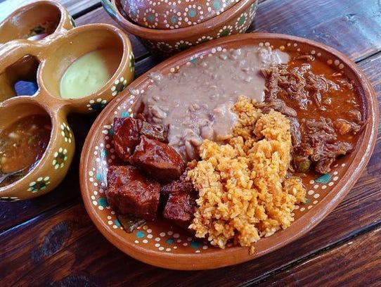 Carne de cerdo con salsa en chile rojo y nopales (izquierda)