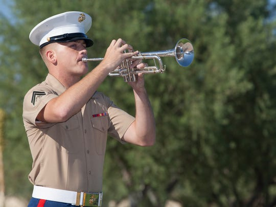 A Marine with Marine Band San Diego plays taps during