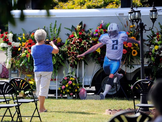 Melissa Sanders takes a picture of a memorial for Rob Bironas at his funeral on Thursday Sept. 25, 2014, in Nashville, Tenn.