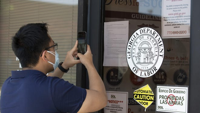 A man uses his phone to take a photo of phone numbers posted on the locked doors of a Georgia Department of Labor office on Thursday, May 7, 2020, in Norcross.