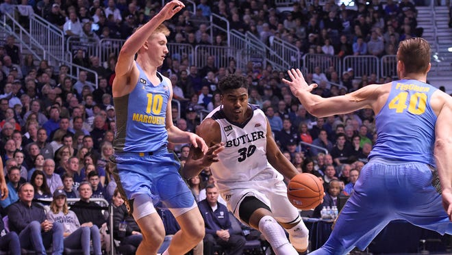 Butler's Kelan Martin dribbles between Marquette's Sam Hauser (left) and Luke Fischer (right) during their first meeting this season in Indianapolis.
