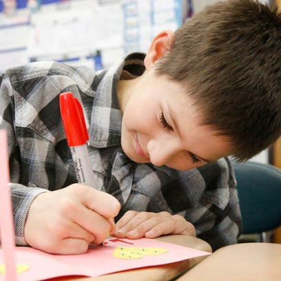 """Dominic Hoppe, 9, fills in the word """"love"""" on a valentine"""