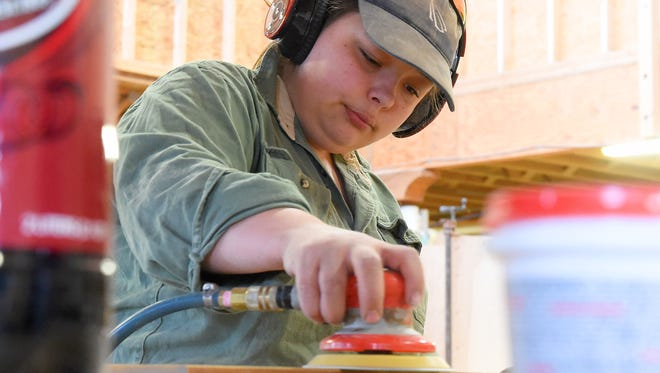 Morgan Bean uses a sander to smooth the sides of a board at Modern Boy Woodshop in Staunton on Friday, April 3, 2015.