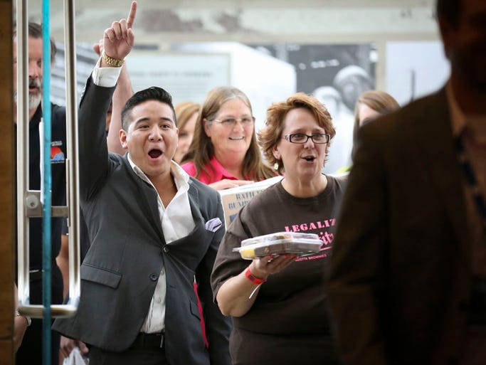 "Phillip Campos, left, of Tre Mentes sala of Des Moines and Michelle Kaiser of Allotta Brownies of Fremont, Nebraska, cheer as they enter the doors to the Iowa Events Center during an open casting call for the ABC show ""Shark Tank"" in Des Moines, Iowa, Monday July 14, 2014."