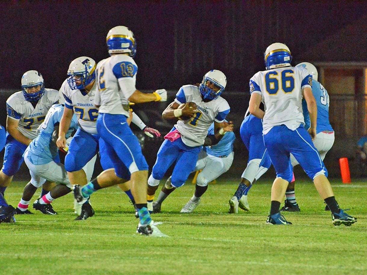 With plenty of blocking, Titusville's Yusuf Dereese runs for a first down Friday night at Rockledge.