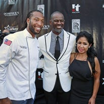 Larry Fitzgerald greets singer Brian McKnight and Leilani Mendoza as they arrive on the red carpet for the Larry Fitzgerald's 7th Annual Fitz's Supper Club event at Dominick's Steakhouse on Aug. 31, 2015, in Scottsdale.