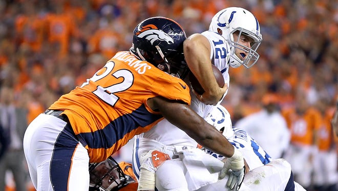 Indianapolis Colts Andrew Luck is tackle by Denver Broncos Sylvester Williams and Derek Wolfe in the fourth quarter. The Indianapolis Colts play the Denver Broncos Sunday, September 7, 2014, evening at Sports Authority Field at Mile High in Denver CO.