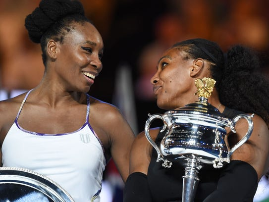 Venus and Serena Williams share a laugh after the trophy