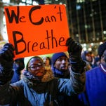 A woman holds a sign as she takes part in a protest following yesterday's decision by a Staten Island grand jury not to indict a police officer who used a chokehold in the death of Eric Garner in July.