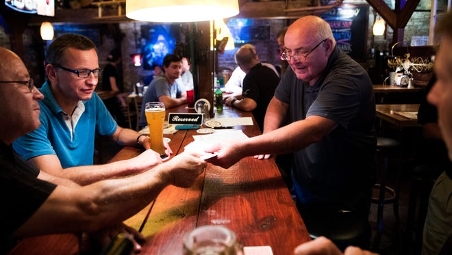 "Bernd Birnbaum, formerly of ZF Lemfoerder, hands out playing cards as he plays ""Skatabend,"" a German game, during a weekly meet up with friends at Hans & Franz Biergarten on Tuesday, June 20, 2017."