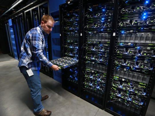Matt Patterson, a data center technician, opens a drawer