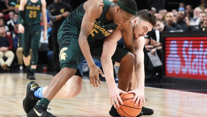 Andrew Platek (3) of the North Carolina Tar Heels and Cassius Winston (5) of the Michigan State Spartans go after a loose ball in the second half.