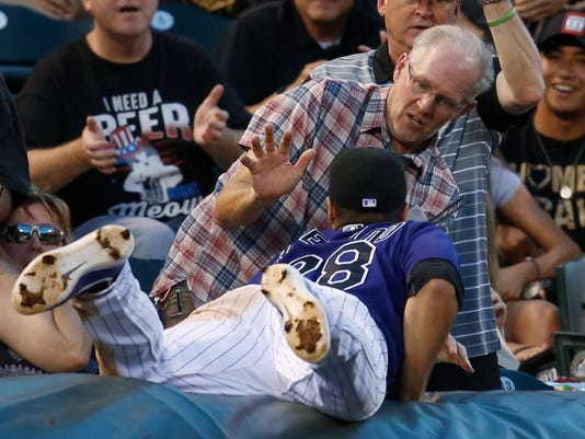Colorado Rockies third baseman Nolan Arenado, front, dives on the tarpaulin but fails to pull in a foul pop off the bat of Philadelphia Phillies' Ryan Howard in the seventh inning of a baseball game Friday, July 8, 2016, in Denver. The Phillies won 5-3. (AP Photo/David Zalubowski)