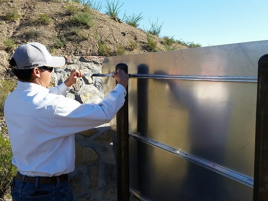 BLM employee Andres Montoya helps install the first-ever entrance sign at the Prehistoric Trackways National Monument in the Robledo Mountains, northwest of Las Cruces, on Saturday