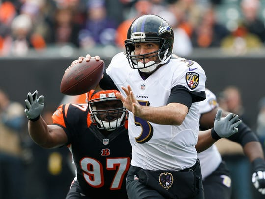 In this Sunday, Jan. 1, 2017 file photo, Baltimore Ravens quarterback Joe Flacco (5) looks to pass under pressure from Cincinnati Bengals defensive tackle Geno Atkins (97) in the first half of an NFL football game in Cincinnati. The AFC North revolves around QB longevity, except in Cleveland. No team in the division has been affected by injuries more than the Ravens, who are at it again. Flacco didn't play in the preseason because of a bad back the opener in Cincinnati will mark his debut.